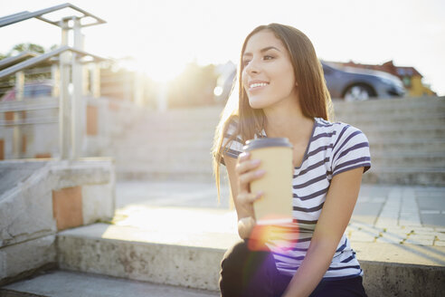 Young woman sitting on stairs outdoors and holding coffee - BSZF00068