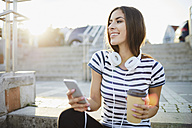 Woman with headphones sitting on stairs in the city with smartphone and coffee - BSZF00071