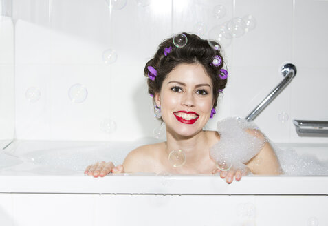 Portrait of smiling young woman with curlers in bath - PNEF00118