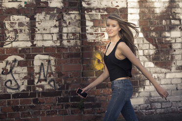 Portrait of young woman with cell phone walking in front of brick wall - PNEF00128