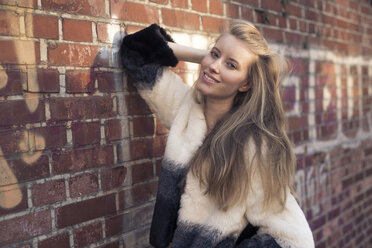 Portrait of smiling young woman wearing artificial fur jacket - PNEF00131