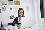 Smiling young woman using laptop at desk in office - PNEF00136