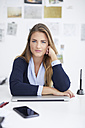Portrait of young woman at desk in office - PNEF00142