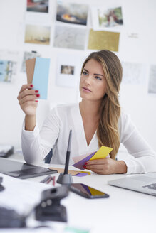 Young woman looking at notes at desk in office - PNEF00145