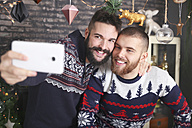 Portrait of happy gay couple taking selfie with smartphone at Christmas time at home - RTBF01036