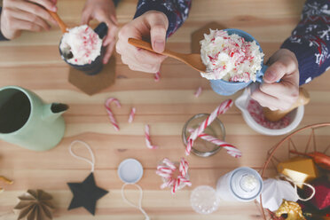 Gay couple preparing hot chocolate with cream and chopped candy canes at Christmas time, top view - RTBF01039