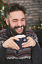 Portrait of laughing man drinking hot chocolate with whipped cream and chopped candy canes - RTBF01042