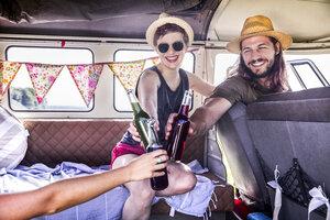Happy friends inside van clinking bottles - FMKF04527