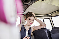 Portrait of smiling woman inside a van - FMKF04530