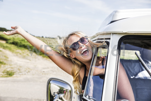 Carefree woman leaning out of window of a van - FMKF04539
