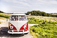 Happy friends inside van in rural landscape - FMKF04542