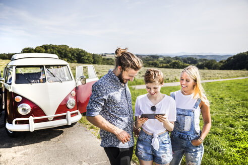 Happy friends outside van in rural landscape looking at tablet - FMKF04545
