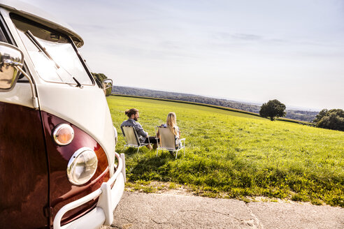 Couple sitting on camping chairs next to van in rural landscape - FMKF04548