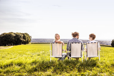 Friends sitting on camping chairs in rural landscape - FMKF04551