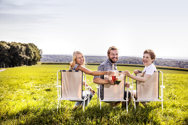 Happy friends sitting on camping chairs in rural landscape clinking bottles - FMKF04554