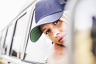 Young woman looking out of window of a van - FMKF04563