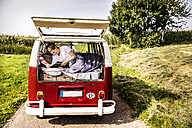 Happy woman lying in a van in rural landscape reading book - FMKF04566