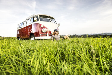 Young man sitting at a van on field in rural landscape - FMKF04575