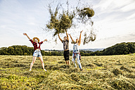 Carefree friends throwing hay in a field - FMKF04578