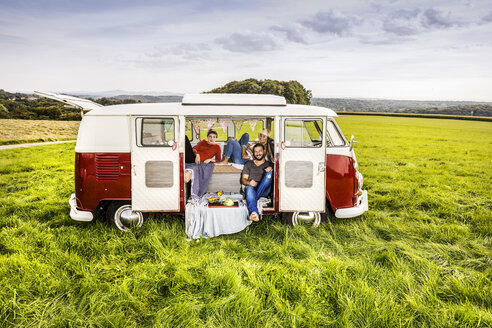 Friends having picnic in a van parked on field in rural landscape - FMKF04584