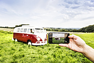 Woman's hand taking cell phone picture of van in rural landscape - FMKF04590