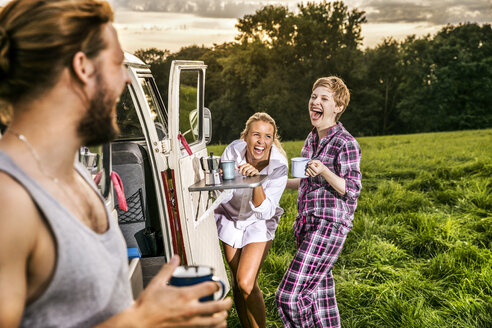 Carefree friends enjoying coffee at a van in rural landscape - FMKF04596