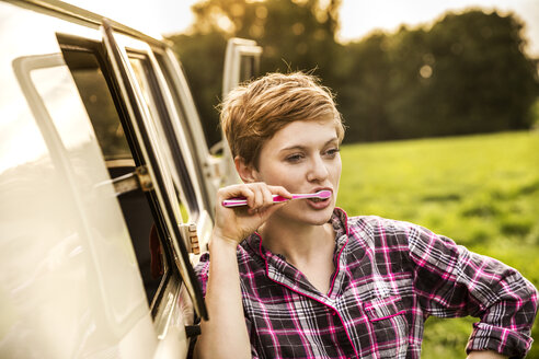 Woman in pyjama brushing teeth at a van in rural landscape - FMKF04599