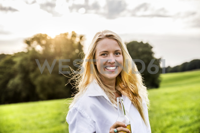 Portait of happy woman drinking beer in rural landscape - FMKF04605 - Jo Kirchherr/Westend61