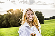 Portait of happy woman drinking beer in rural landscape - FMKF04605