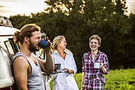 Carefree friends enjoying coffee at a van in rural landscape - FMKF04608