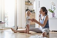 Portrait of happy baby girl with mother at home - DIGF02895