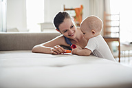 Baby girl with mother playing on couch at home - DIGF02898