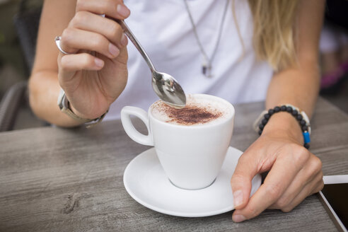 Close-up of woman with cappuccino in a street cafe - JUNF00919
