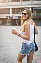 Smiling young woman holding takeaway coffee in the city - JUNF00922