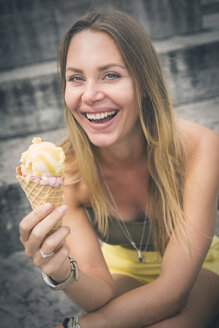 Portrait of happy young woman holding ice cream cone - JUNF00925