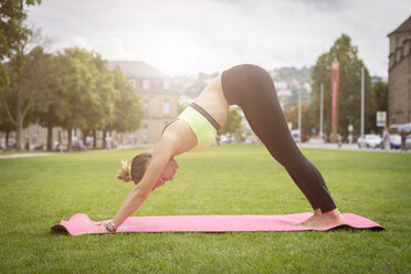 Young woman practicing yoga in a park in the city - JUNF00928