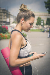 Young woman with yoga mat, cell phone and earphones in the city - JUNF00931