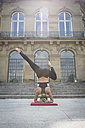 Young woman doing a headstand during a yoga exercise in the city - JUNF00934