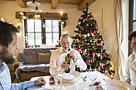 Smiling senior man with family holding bottle of wine at Christmas dinner table - HAPF02180