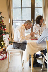 Senior man with family dining at Christmas dinner table - HAPF02195