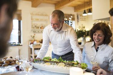 Senior man serving fish for family at Christmas dinner - HAPF02201