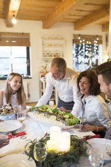 Senior man serving fish for family at Christmas dinner - HAPF02204