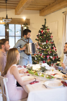 Young man playing accordion at Christmas dinner table - HAPF02207