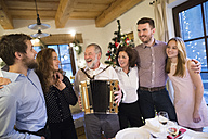 Senior man playing accordion for happy family at Christmas - HAPF02213