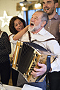 Senior man playing accordion for happy family at Christmas - HAPF02216