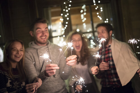 Happy friends holding sparklers outdoors at night - HAPF02222