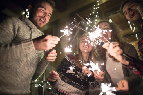 Happy friends holding sparklers outdoors at night - HAPF02225