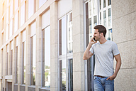 Man walking in the city, making a phone call - JUNF00939
