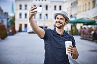 Man taking selfie in the city with coffee and fedora hat - BSZF00080