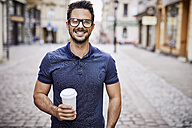 Portrait of a smiling man with glasses holding coffee outdoors - BSZF00086